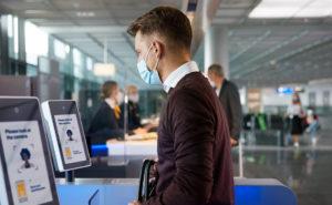 Man wearing a mask standing at the biometrics kiosk