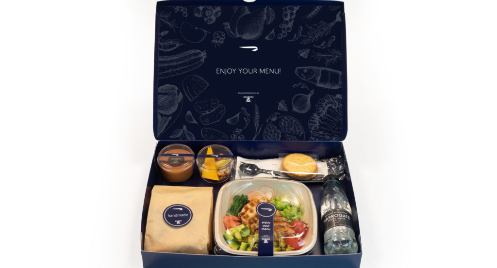 A box containing various plastic-wrapped or enclosed dishes including a salad and sides, plus a bottle of water.
