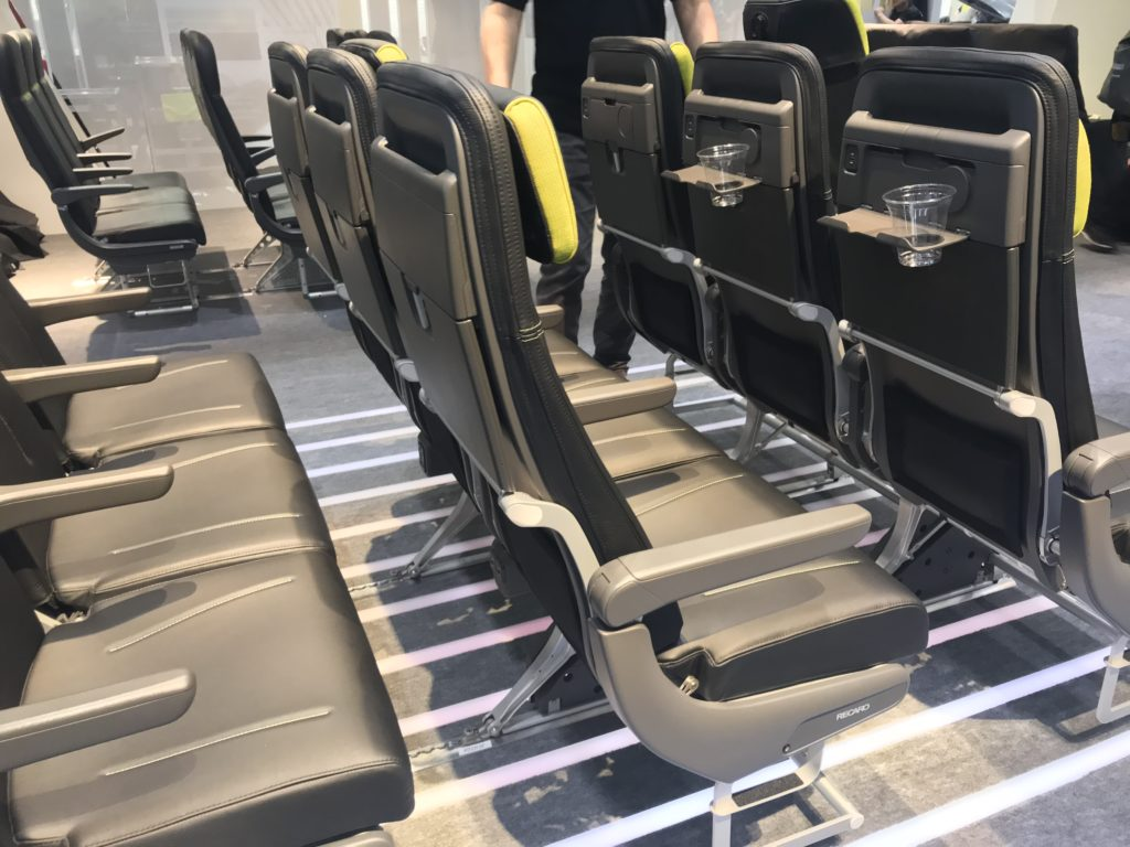 Rows of BL3710 seats on a show floor, showing the full features of the seat, including headrest and cupholders