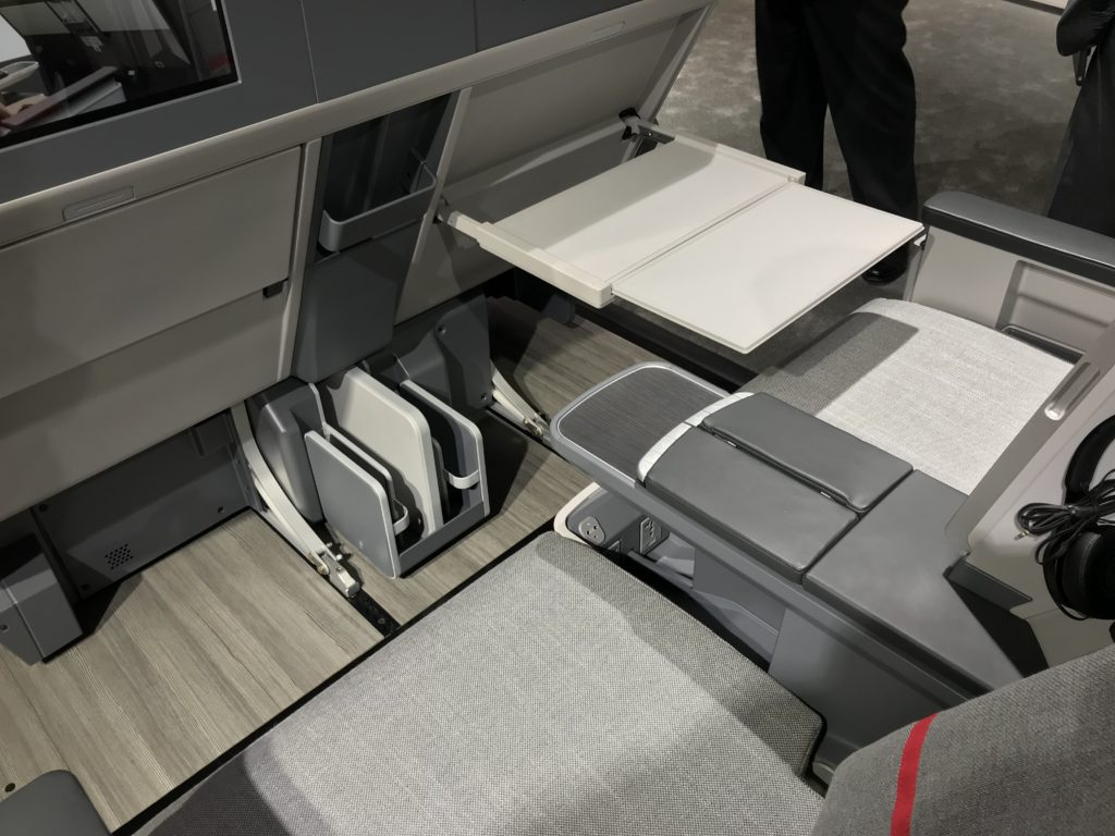 A photo of the Collins Aerospace Air Rest recliner on a show floor. The seat is covered in grey material.