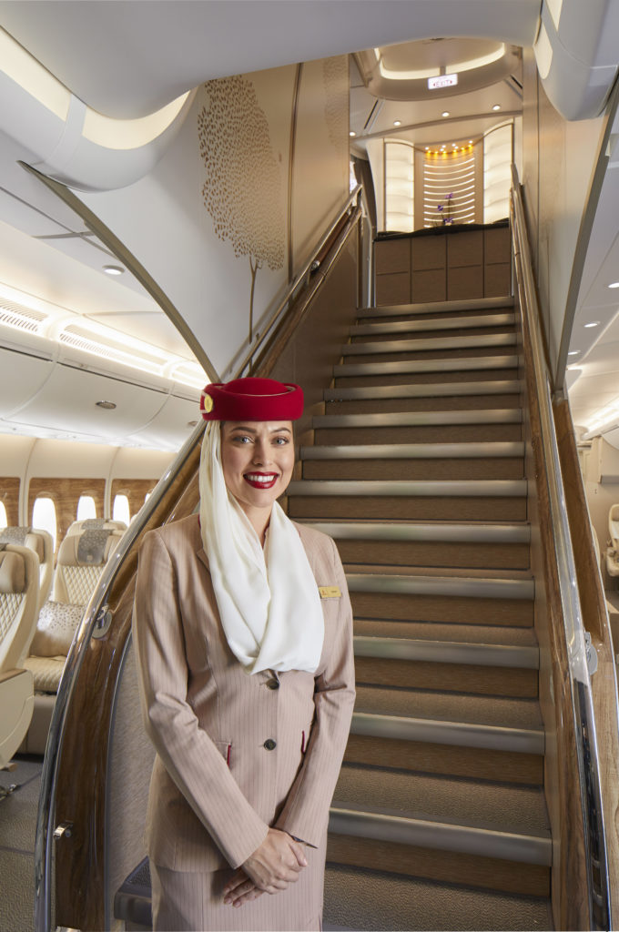 A flight attendant stands at the bottom of the stairs aboard the Emirates A380