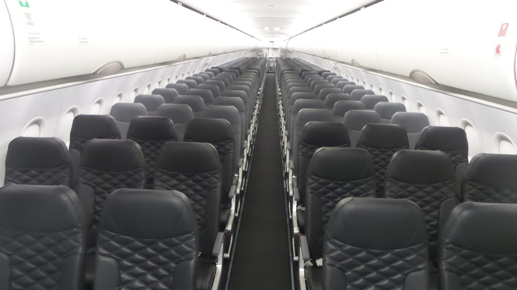 Rows of slimline economy class seats in dark greyish black