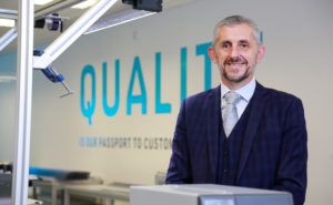 """STG Aerospace's new CEO, Grant Bennett is pictured in front of a sign saying """"quality"""""""