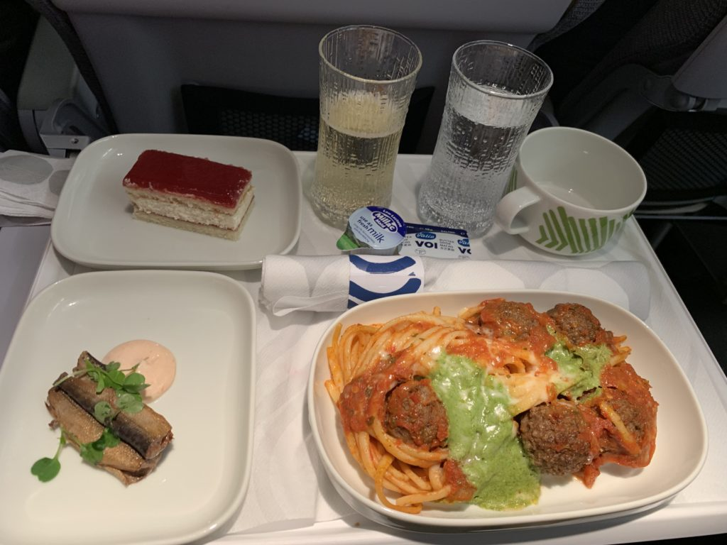 An aircraft tray table with a main course of pasta, a side dish and a dessert with champagne and water.