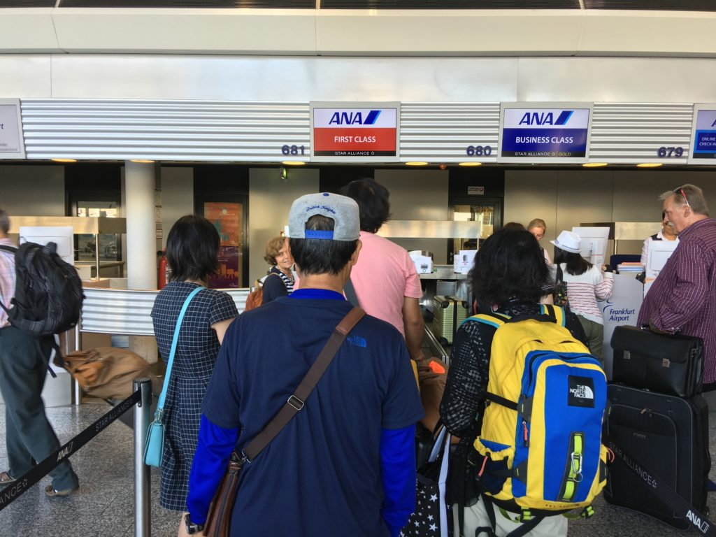 Passengers lined up at an All Nippon Airways airport counter