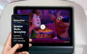 """A seatback screen showing a cartoon in-flight. A man's hand is seen holding up a device which states: """"QuiverTree: Aviation Media Specialists"""""""