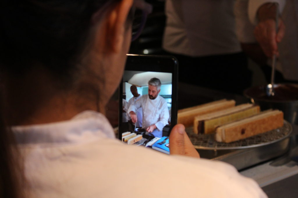 A cooking class is seen on a woman's mobile device.