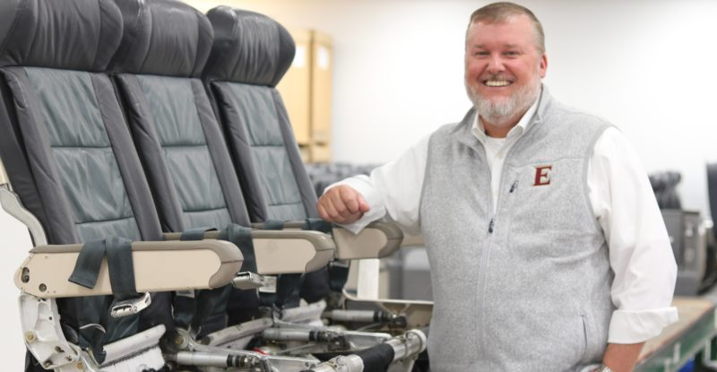 Kelvin Boyette CEO of Latitude Aero standing beside 3 aircraft seats on display