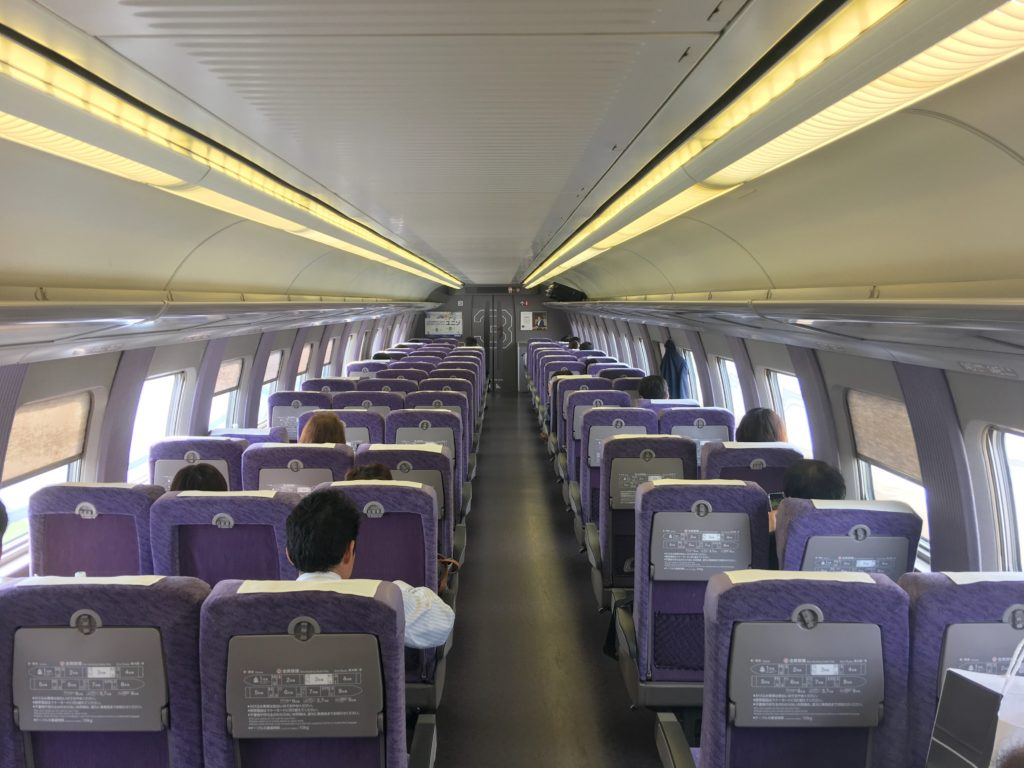 An view from the back of a Shinkansen car showing rows of purple seats, five-abreast (3-2)