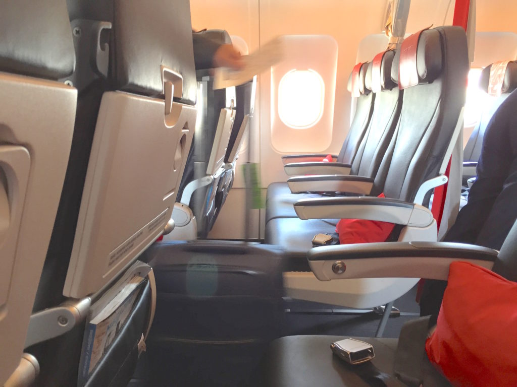A row of economy class seats with blue seat covers and red pillows as accents