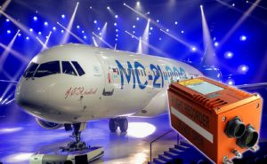 MC-21 Aircraft and a imaging multi-purpose flight recorder with a bright blue background with multiple light streams