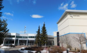 SD Ottawa facility external view with two pine trees and clear blue sky
