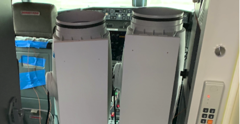 Two tall grey thermal sanatizes in the cockpit of a Boeing aircraft