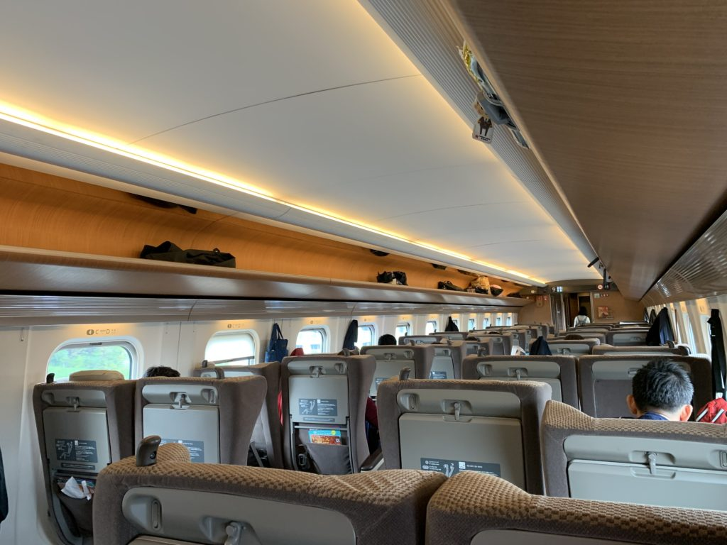 Seats configured in a 2-2 layout in business class, with beige material on the seats and orange-colored overhead bin space