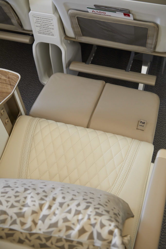 The new double calfrest for premium economy is shown. Cream-colored seat covers are seen, as well as a decorate pillow.