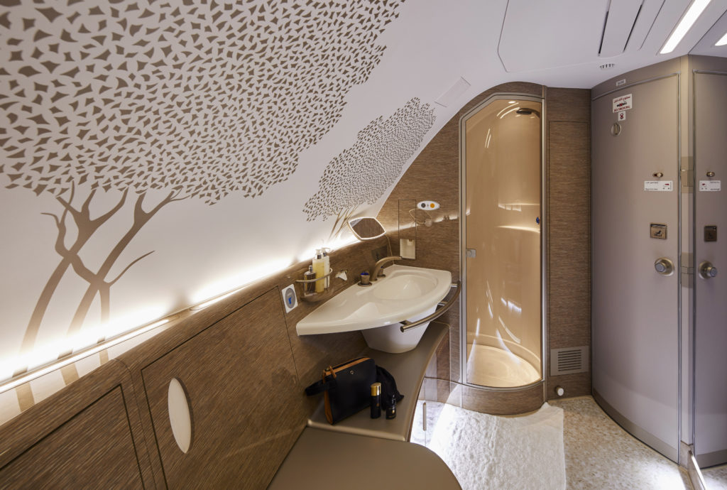 The first class shower aboard Emirates' A380 is shown. The ghaf tree design is seen on the wallpaper.