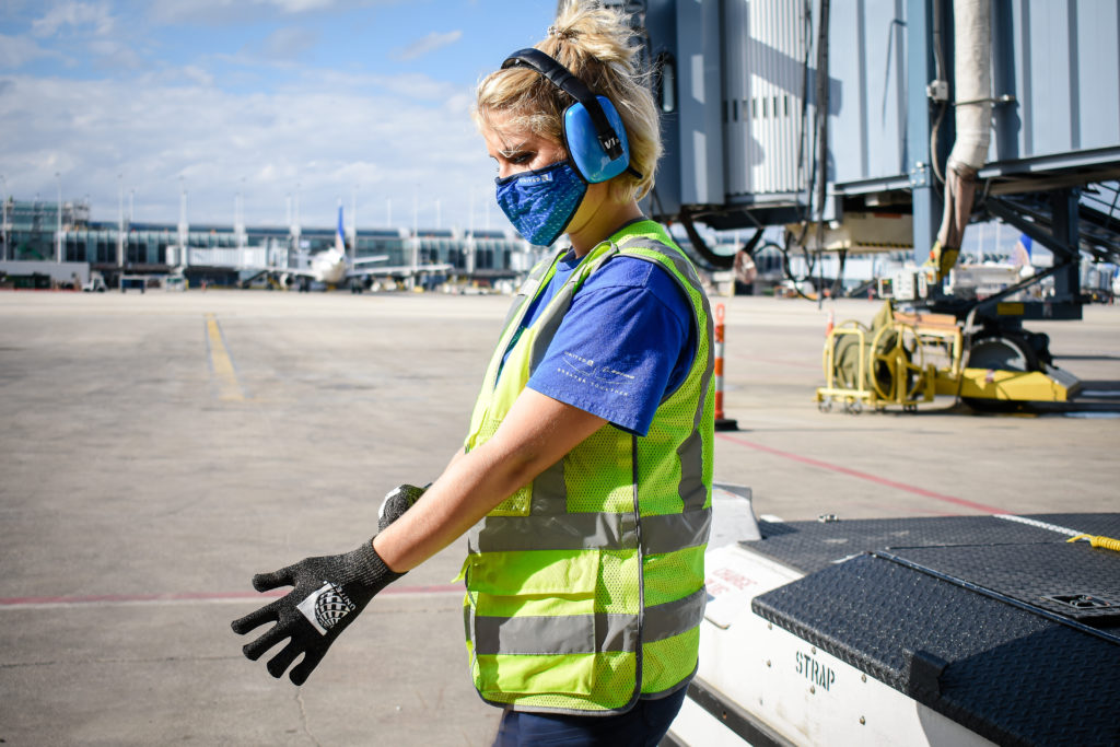 A female airline ground handler at the airport. She is wearing a bright yellow jacket, a headset and gloves. A jetway is shown in the background, as well as the tail of a parked aircraft at the gate.
