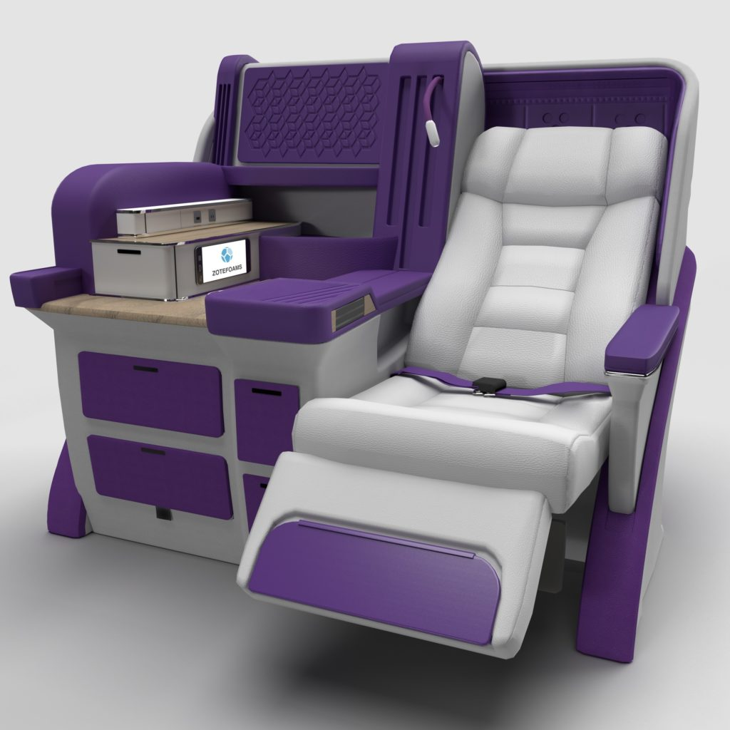 A premium class seat in grey surrounded by various foam structures in purple, including armrest and storage spaces
