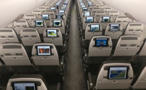 Rows of slimline seats on an Airbus narrowbody with tablets fixed to the back of the seats, showing streaming content