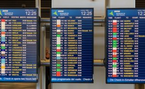 Three side-by-side monitors at the airport, displaying flight information