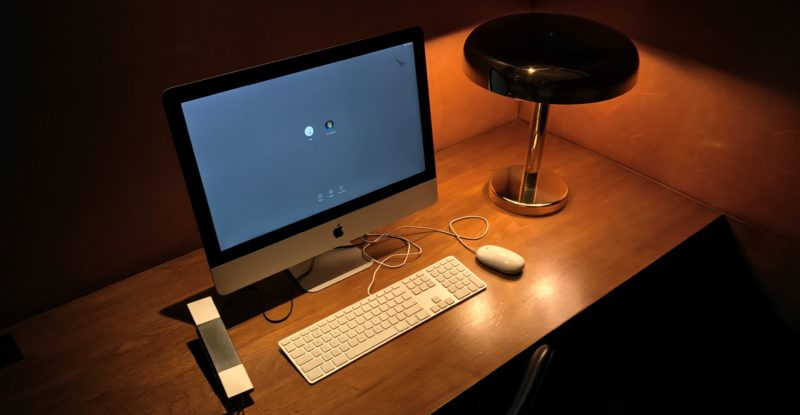 A brown wooden table in a lounge. A computer screen, a keyboard, a light and a landline phone sit on the table.