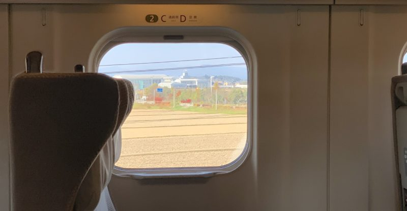 A side view of a seat aboard a Shinkansen, with a view out the window showing Japanese countryside