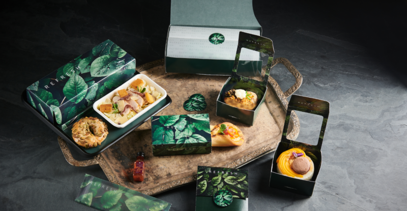 A boxed-up inflight lunch consisting of individually packed salad, sandwich and dessert