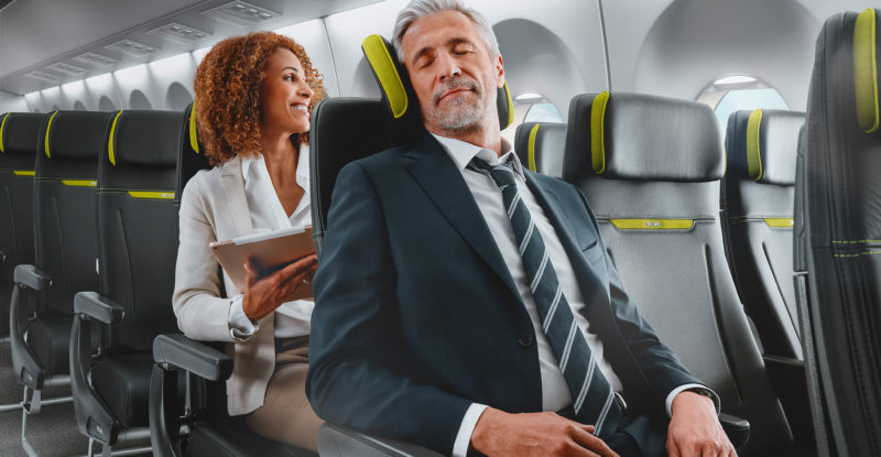 A man sleeps in an economy class seat with a headrest propping up his head.