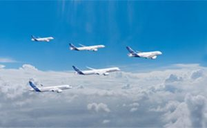 Multiple airbus aircraft inflight over top of clouds with a clear sky above them
