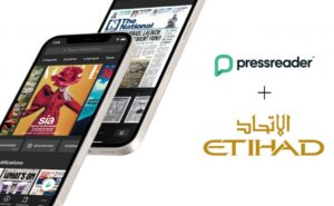 Tow mobile phones showing different newspaper apps with next tp the pressreader and etihad logos