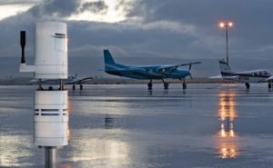 A variety of aircrafts on wet tarmac with a dark cloud filled sky in the background, and a weather tracker in the foreground