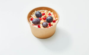 Bircher Muesli displayed in a brown bowl on the center of a white background