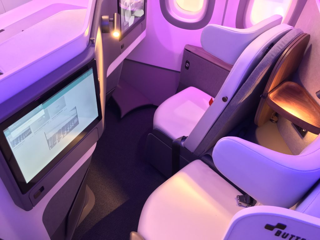 A pink and purple LED light-lit close-up of the Butterfly convertible seat, with in-seat IFE screen in view