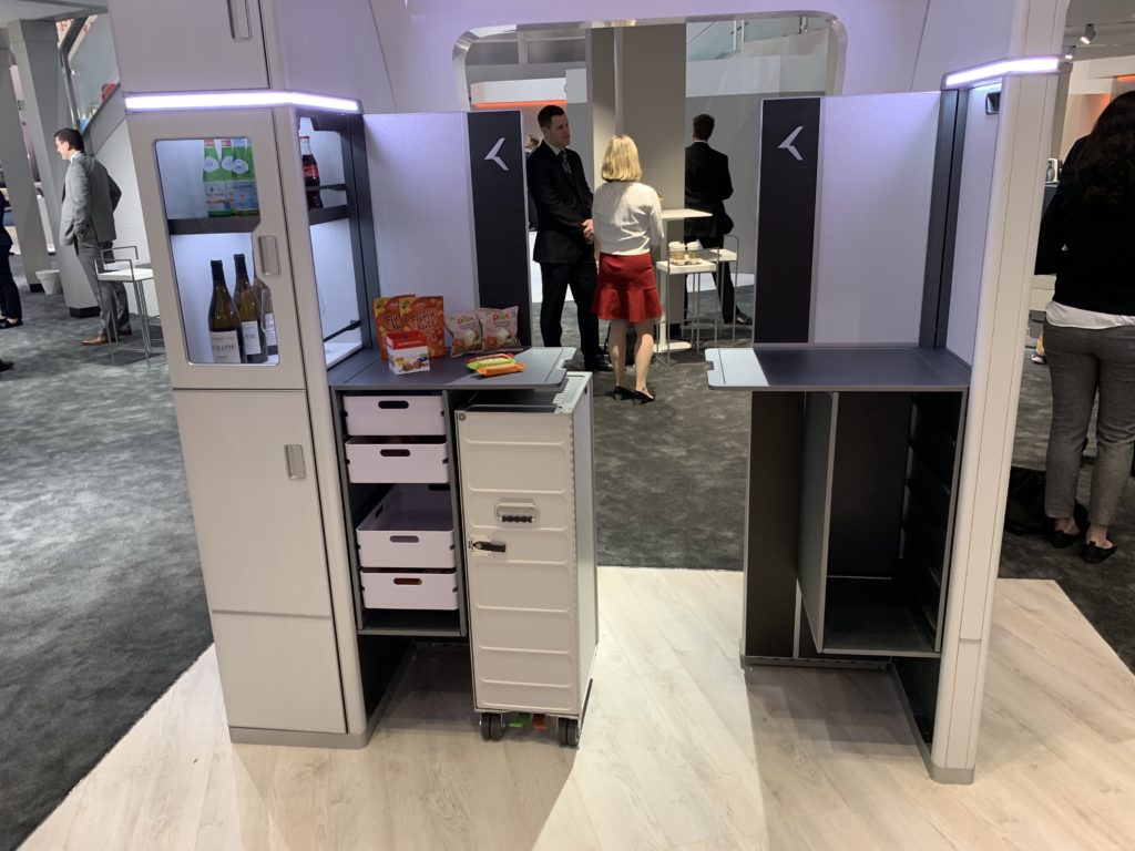 Collins M-Flex is a fold-out monument for bars, lounges, self-service areas, ancillary revenue sales spaces, promotional areas, and more. It is shown here on a show floor, with bottles of win seen in the display.
