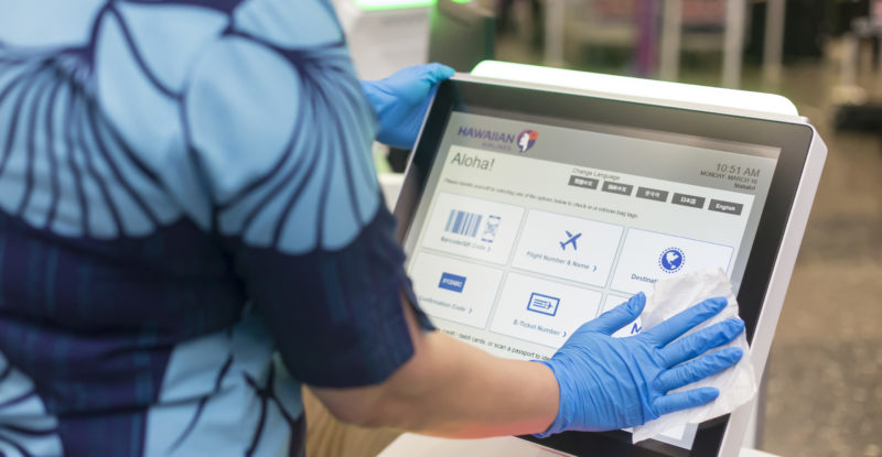 Hawaiian airlines employee wiping down a check in kiosk