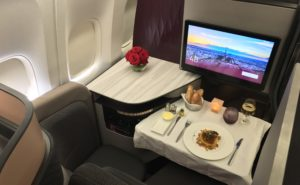Business class aboard Qatar Airways, with a large IFE screen and a rose accent