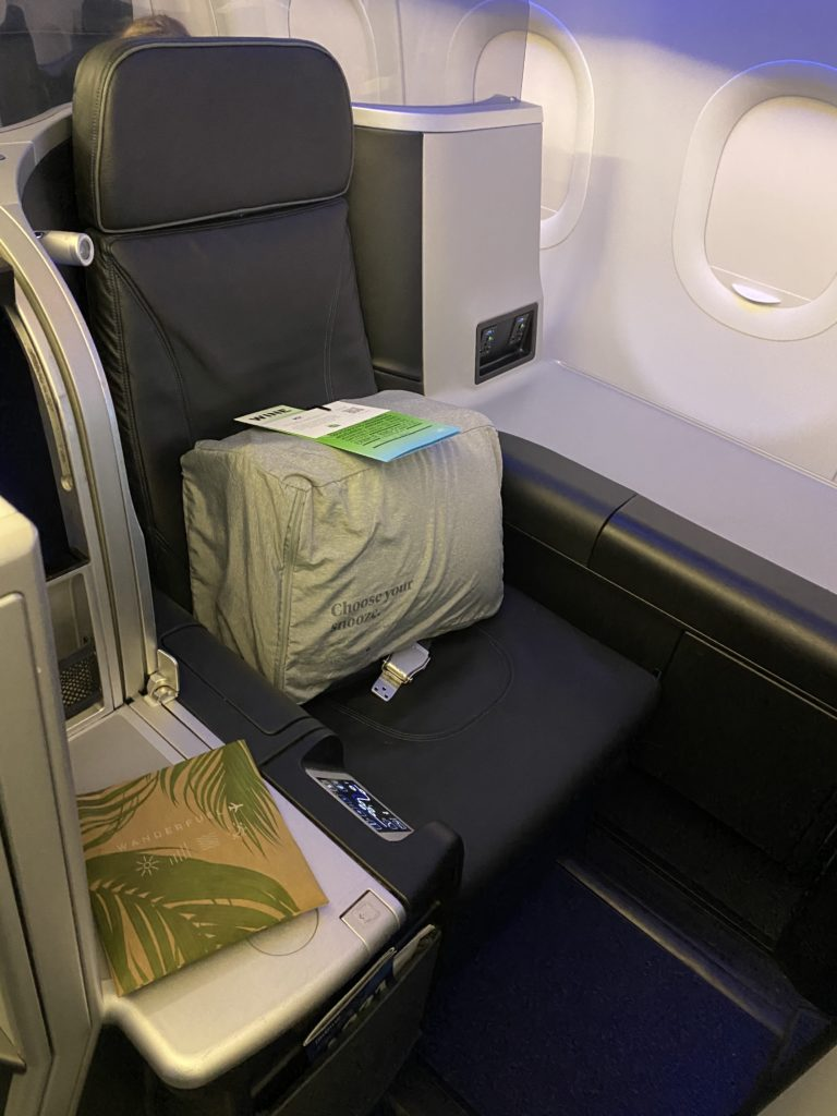 A bag of fresh bedding sits atop the Mint business class seat.