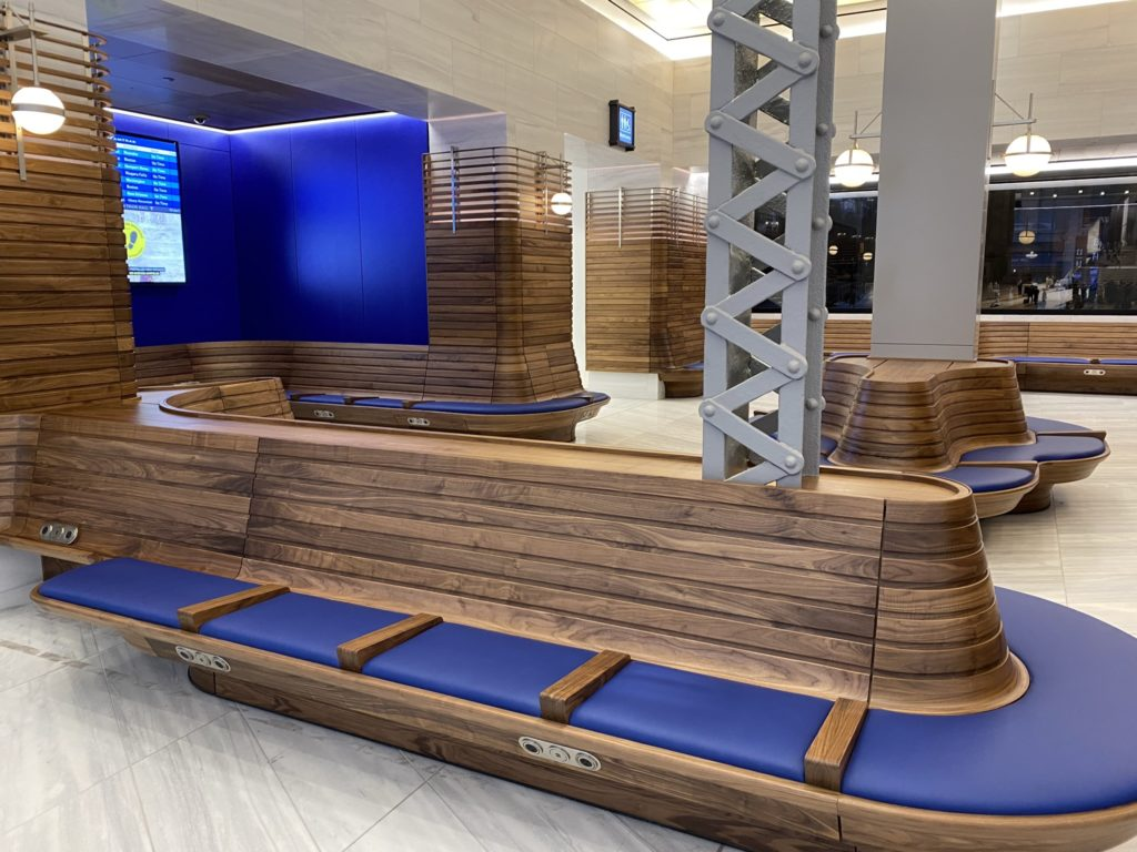 Benches with blue padding, and wood accents in the ticketed passenger waiting area