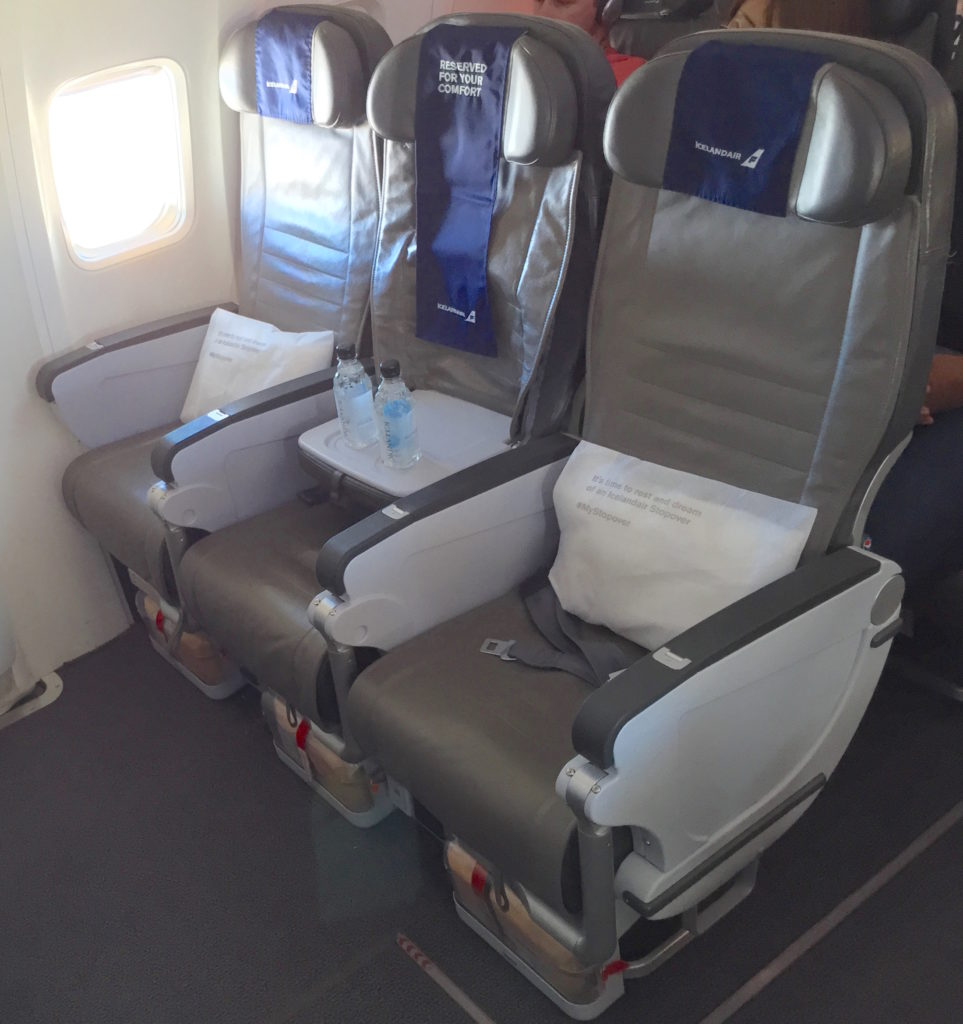 A photo of Icelandair's prior middle-seat-free premium economy product. A small table on the middle seats gives window and aisle passengers a place of their water bottles