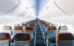 JetBlue A220 view from the front showing light grey seats with a dark grey headrest and orange trim.