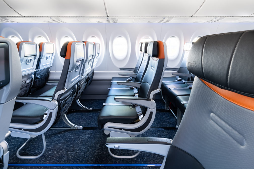 JetBlue A220 side view from the aisle, showing slimline seats with headrests, and seatback IFFE