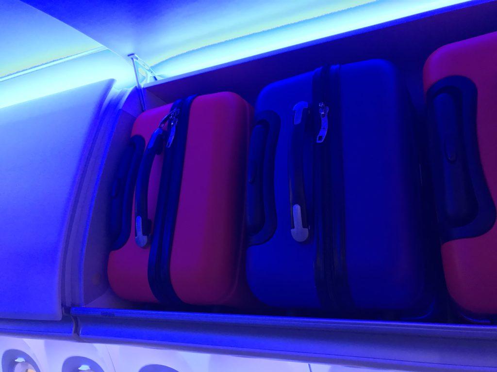 Carryon bags in a row in the overhead bin