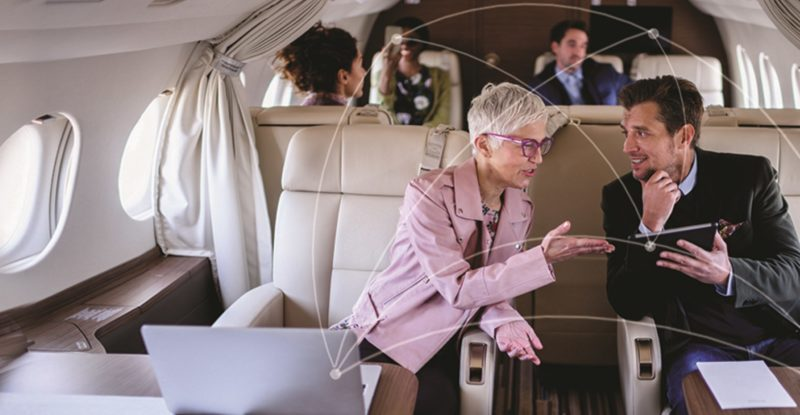 Women in a pick Blazer with shoirt hair talking to a man in a buisness suit on a private Business jet. A few men and women in the background as well.