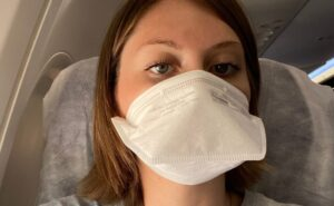 Young woman wears a white mask on board an aircraft