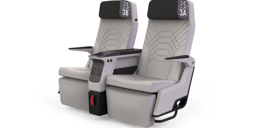 The Aviointeriors Synthesys premium economy seat is picture with black headrests and a light grey seat cover with stitching