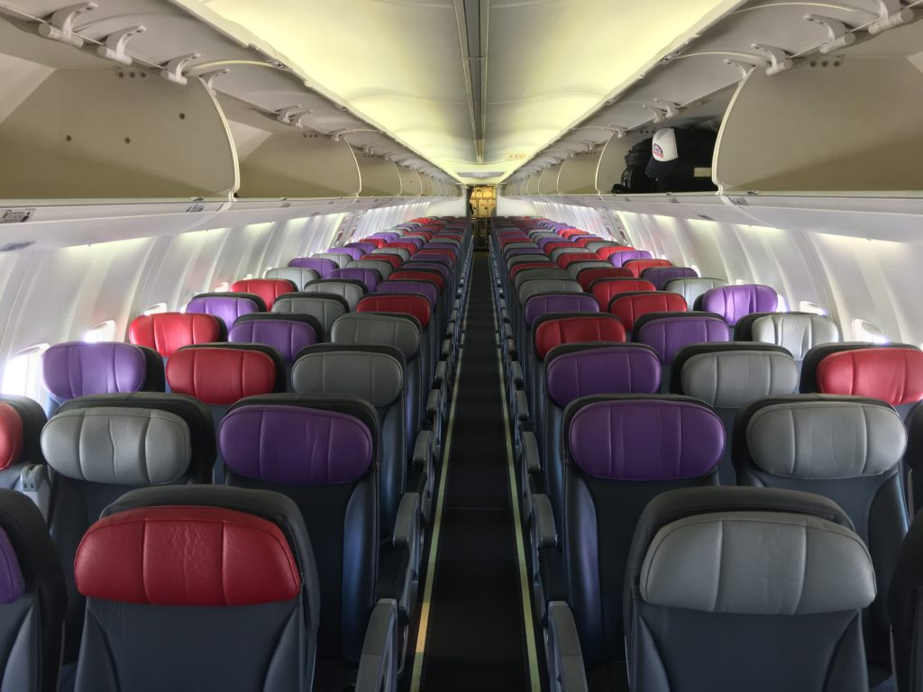 Rows of economy class seats aboard Virgin's 737-800. The headrests feature different colors - red, purple, and grey