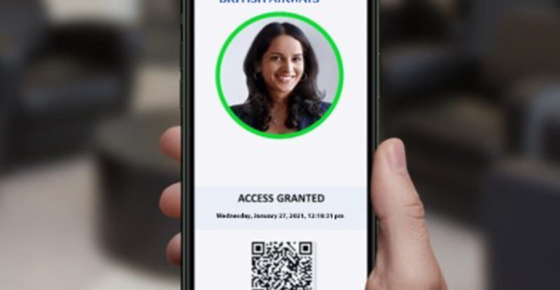 A woman holding up her mobile device showing the verifly landing page with a QR code, photo of the woman and confirmation to fly.