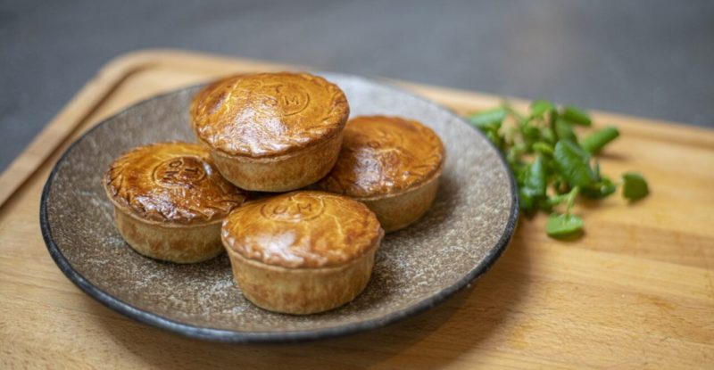 a display of 4 Warm Steak & Ale Pie on a grey plate set atop a butchers block