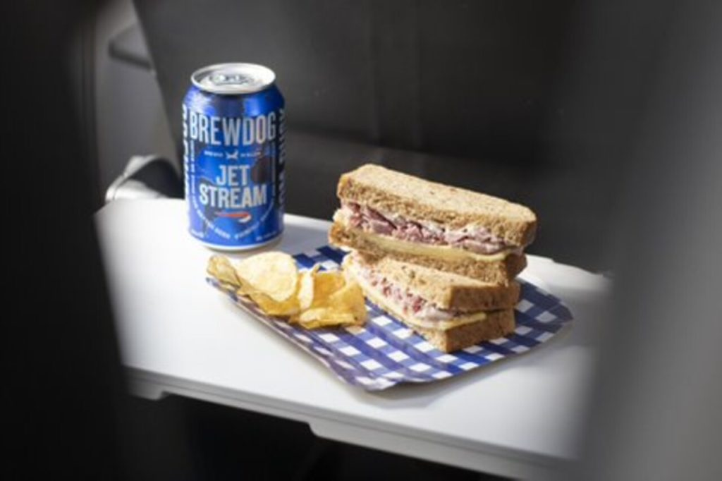 A beer and Sandwhich being displayed on an aircraft seat tray