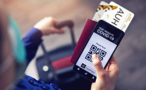 IATA Travel Pass A person holding boarding passes, passport and a mobile device displaying a QR code and the word COVID-19